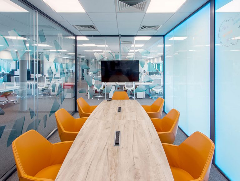 Conference room with orange chairs and writing on wall