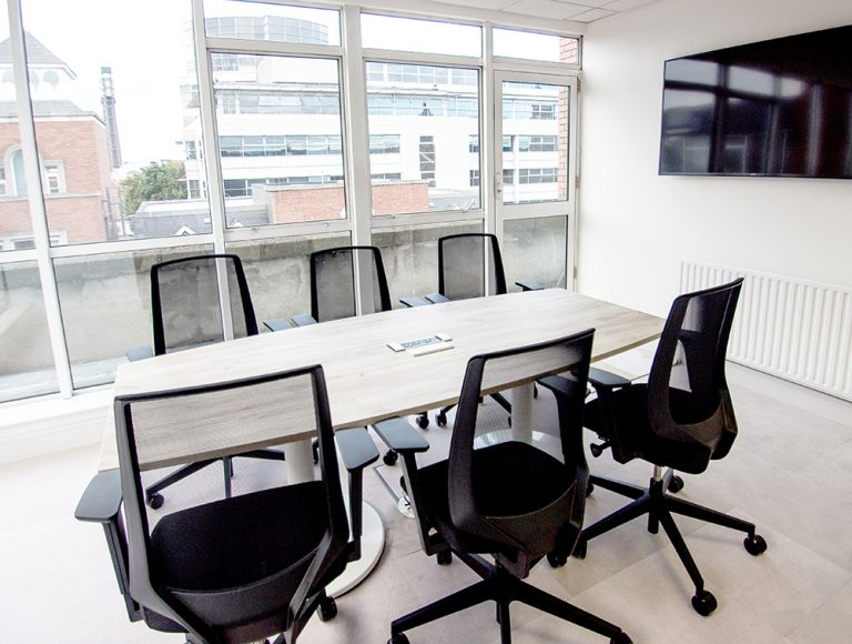 Conference room with six chairs and tv screen embedded on wall