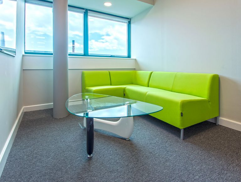 Green soft seating sofa corner with glass table in black and white legs