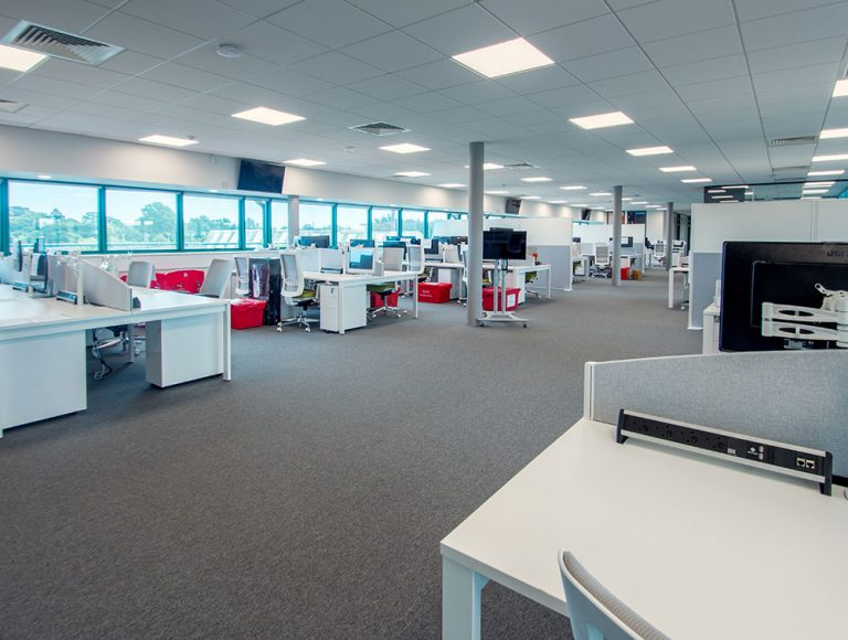 Open office area with white workstations and power modules