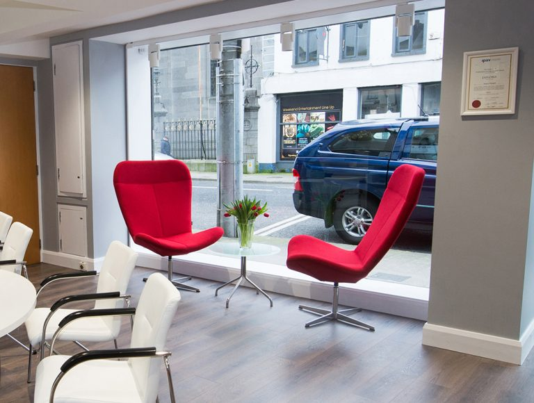 Two red chairs and several white chairs in front of window