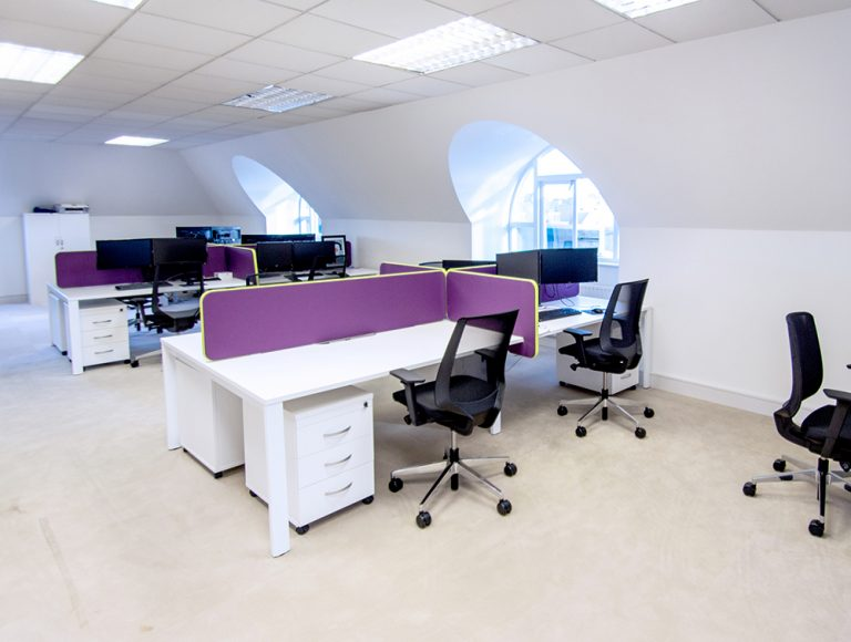White desks with black mesh chairs and purple privacy screens