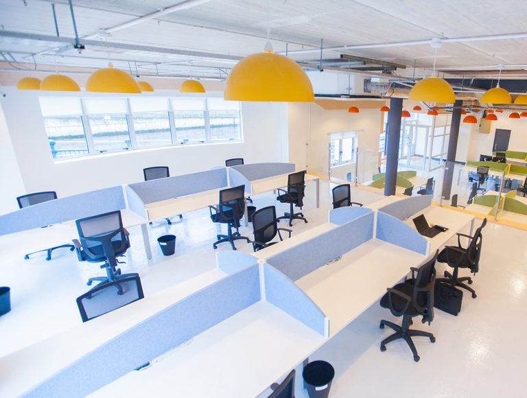 Open office area with white desks, black chairs and privacy screens