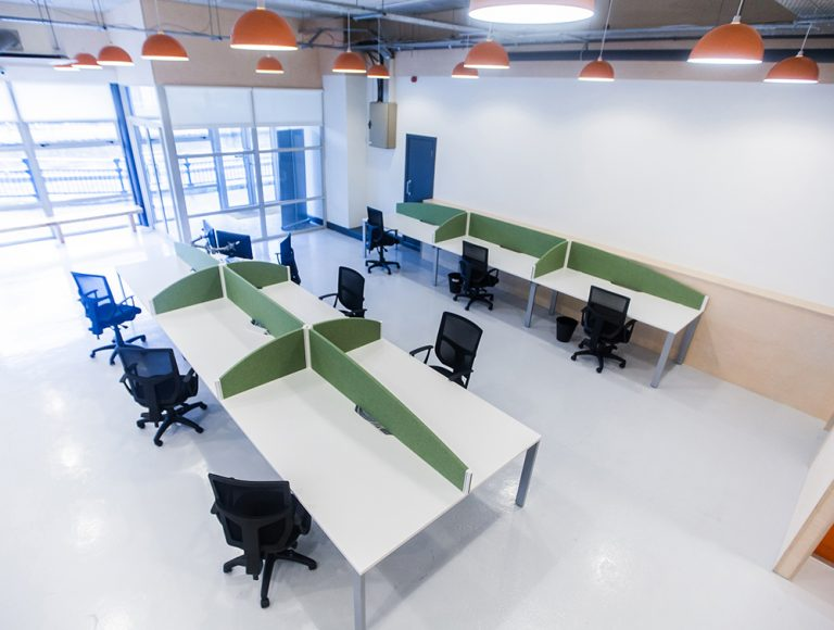 Work areas with green privacy screens and mesh chairs