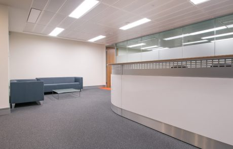 Apex-Office-Layout-White-Reception-Desk-with-Grey-Soft-Seating-and-Glass-Table